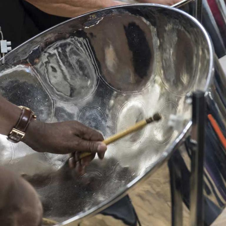 This is a close-up photo of a member of the Glissando Steel Band. The photo focuses on the inside of the steel drum with the players hands in shot