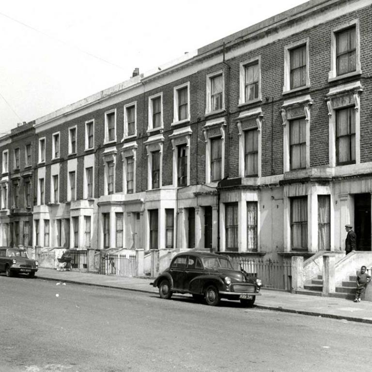 A black and white photo of Wornington Road, looking east before Wornington Green Estate was built, depicting Victorian terrace houses. There is a young boy leaning against a wall as a man comes down the front steps behind him. A pram stands further up the pavement. There are three cars parked on the empty road. Photo courtesy of RBKC Local Studies and Archives, 1970.
