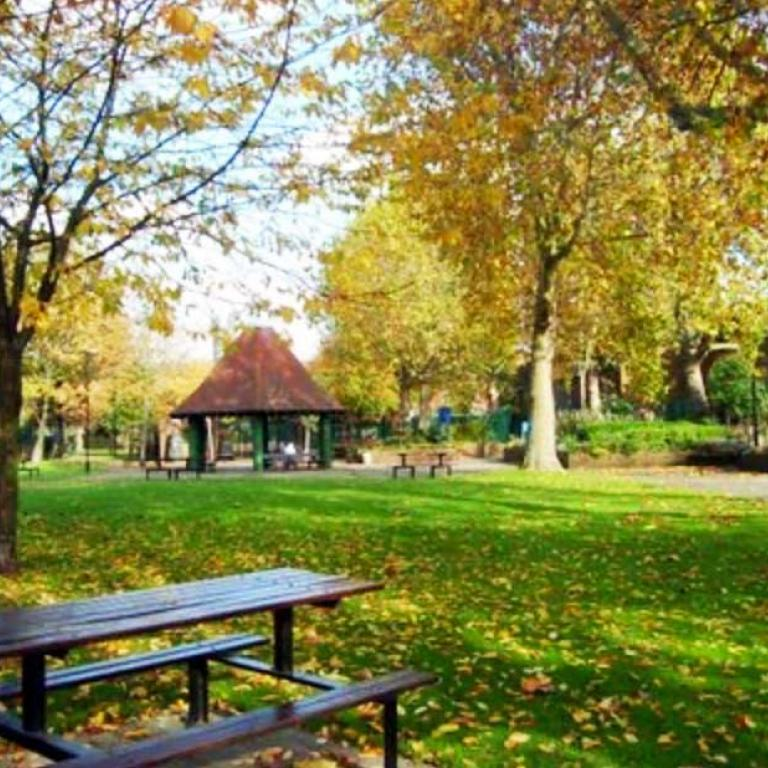 The original Athlone Gardens in Autumn. A brown table with attached benches sits on the grass to the fore. A circular pavilion with a brown roof, known as the 'witches hat' to locals, stands in the background. Tall trees with abundant yellow and orange leaves edge the central expanse of green lawn. Photo reproduced from The United Estate of Wornington Green, 2008.