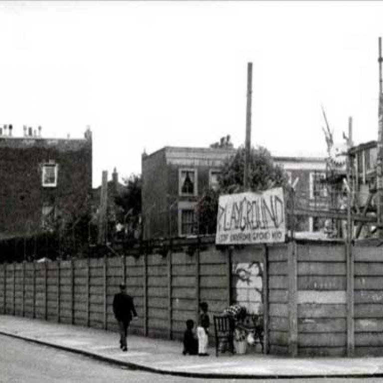 Photo depicts the Notting Hill Adventure Playground from Wornington Road on the south side. On this corner side the playground has a wooden fence with a big sign saying playground attached to the chain link fence atop. In front, on the pavement, is a man painting a mural onto the fence with two young children watching on. Behind in the playground you can see a big higgledy piggledy wooden structure with a boy climbing up one side. To the left on the street and further behind are residential houses.
