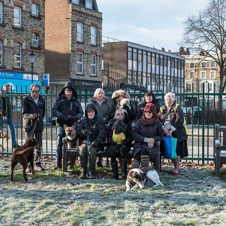 A frost covered grass to the fore. In the centre are nine members of the famous dog walking club sitting on and standing around a bench in coats and scarfs. Three dogs are close by. One called Fidel shares the bench with them as they pose for the camera. A green railing fence is behind them above which is seen AK Foods on Portobello Rd and Lloyd Williamson School on Telford Rd. Photo by Kevin Percival 2019.