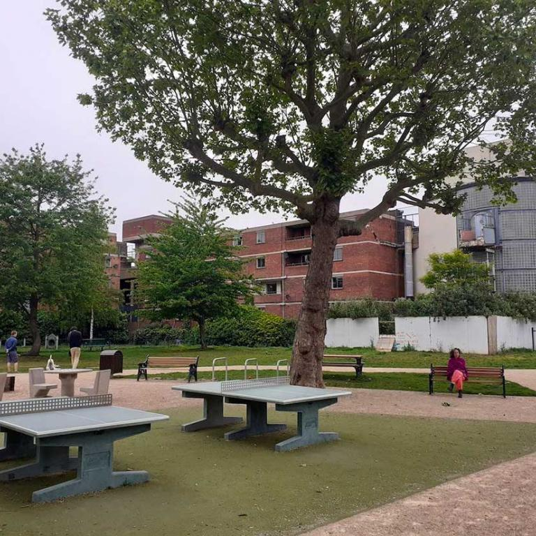 A view in Athlone Gardens from the Portobello Road side. Newly laid table tennis pitches stand beneath a leafy mature tree. Two other trees stand in the background in front of the red bricked Chesterton and Chiltern Houses. To the right is the fenced off and demolished Lionel House walkway and the side of the glass entranceway to Watts House. In the centre a woman sits on a park bench placed on a neat pathway. Photo by Constantine Gras 2020.