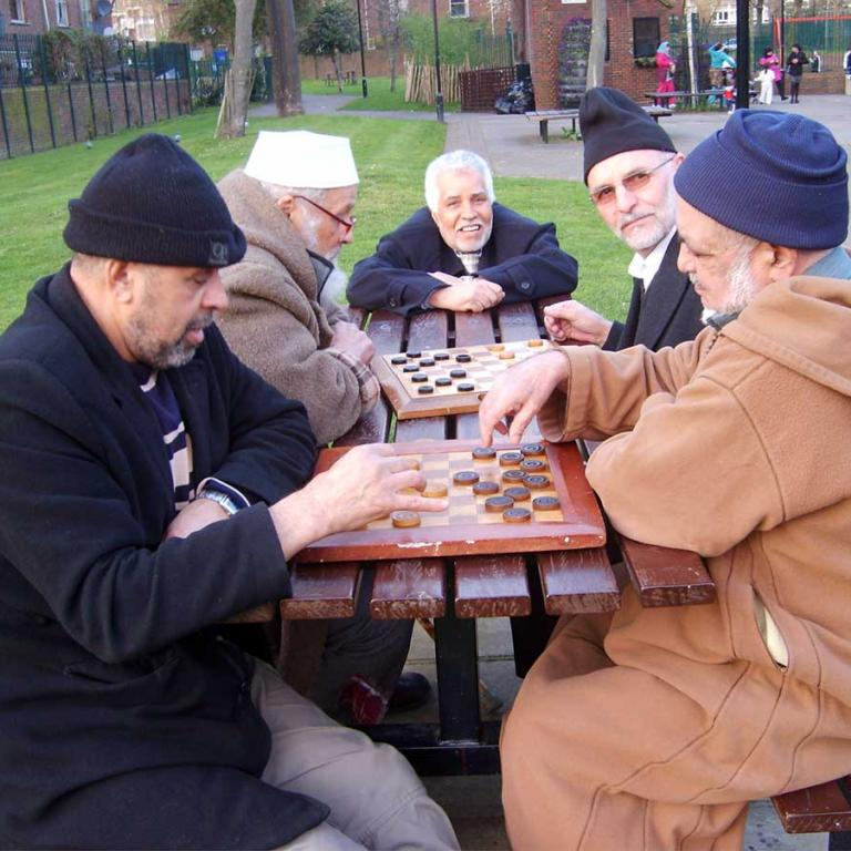 To the fore five men play dominoes as they sit around a brown table. Two look towards the camera. Three are deep in concentration. To the right is the lower half of Wheatsone House. A concrete path winds though the centre. A blackboard leans against a brick wall to the left in the background. Photo reproduced from The United Estate of Wornington Green, 2008.