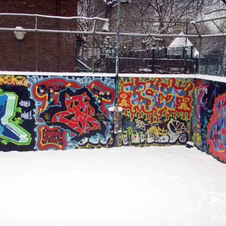 Snow covers the floor of the basketball court highlighting the multi-colours of the two graffitied walls. A metal fence rises above the back wall. Trees and the snow covered cone shaped roof of the witches hat in the original Athlone Gardens can be seen through it. Photo by Junior Tomlin 2012.