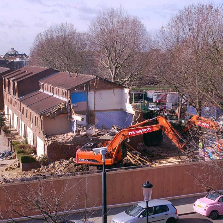 Picture of a partially demolished Faraday House revealing the inside blue wallpaper of a residents former home.  In the foreground rubble, is an orange demolition machine. In the background are trees from the original Athlone Gardens. Photo taken from window of glass and jewellery workshops in Wornington College. Photo by Ken MacDonald, 2011.
