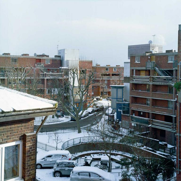 Looking South-East across the estate from Thompson House towards Katherine House. From l to r: Pepler House (left foreground), Katherine House (middle background), Wells House and the community garden, and Rendle House. The ground is covered in snow, on a bright winters day, and a resident clears her car windscreen in the shadow of the buildings in the foreground. Photo by Kevin Percival, a resident of Pepler House, 2018.