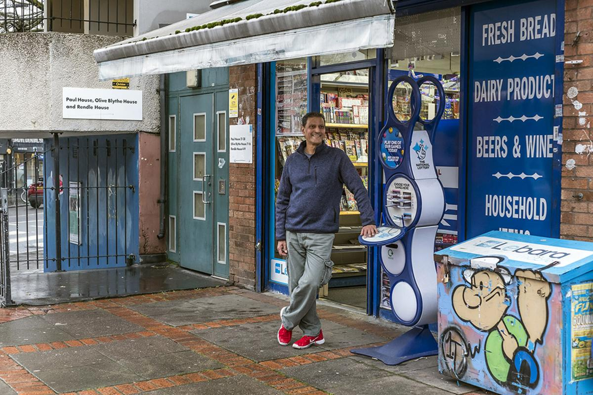 Kirit is standing outside his newsagent shop. There is a taupe coloured door with panels in it to his right and black railings, one end attached to a blue wall. Kirit is leaning on a lotto stand-alone unit with a large padlocked metal box next to it painted with a picture of Popeye. Kirit is wearing a blue collared sweatshirt, light grey commando trousers and red trainers. He has short dark hair.