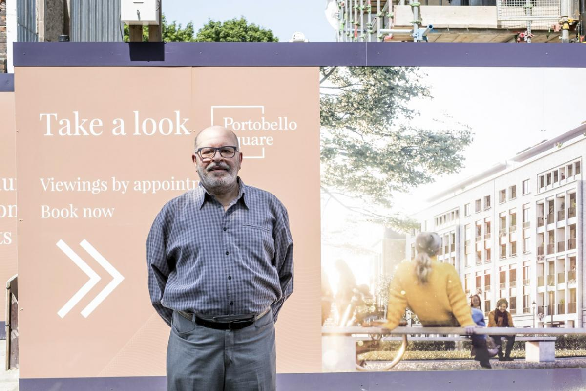 Moshen is standing in front of a huge billboard depicting the new buildings of Portobello Square. He is bald with a grey beard, a grey moustache and black framed glasses. He is wearing a purple checked shirt and a pair of grey suit trousers with a black belt.