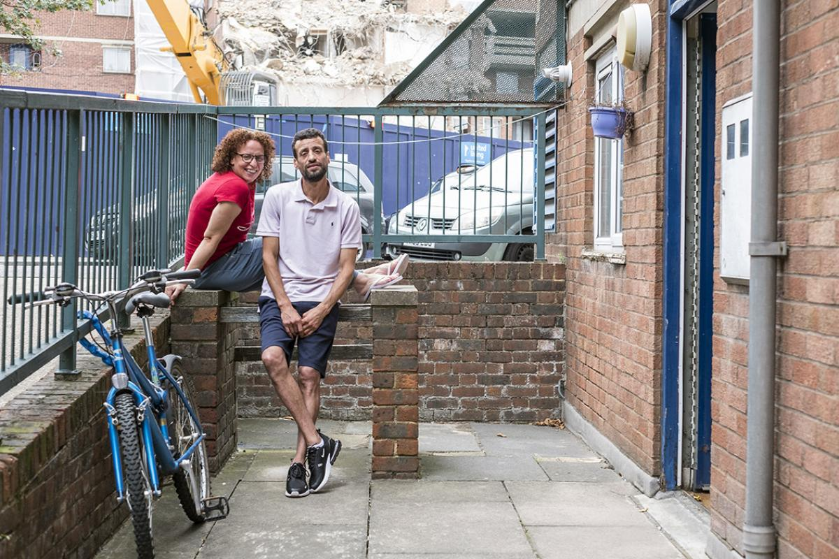 Latifa and Rachid are outside their ground level flat in the courtyard. The blue railings are on street level, the floor is concrete and there is a red brick barbecue unit. A bicycle is chained to the railings. Latifa is wearing a red t-shirt, casual blue trousers, flip flops and she wears glasses. Rachis is wearing blue shorts, a polo t-shirt and black trainers.