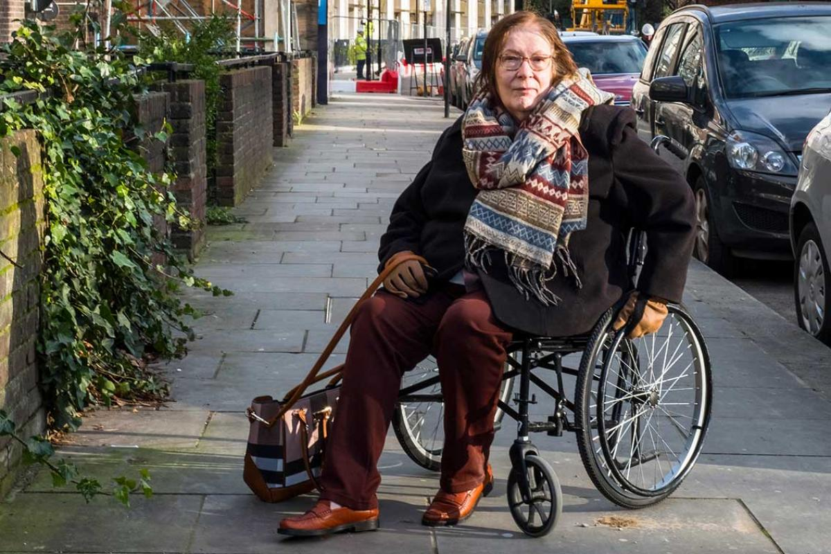 Margaret is in a wheelchair on a pavement with parked cars to her right. She is wearing a striped wool scarf, a black winter jacket, brown leather gloves, brown trousers, brown shoes, a pair of glasses with a handbag looped over one hand.